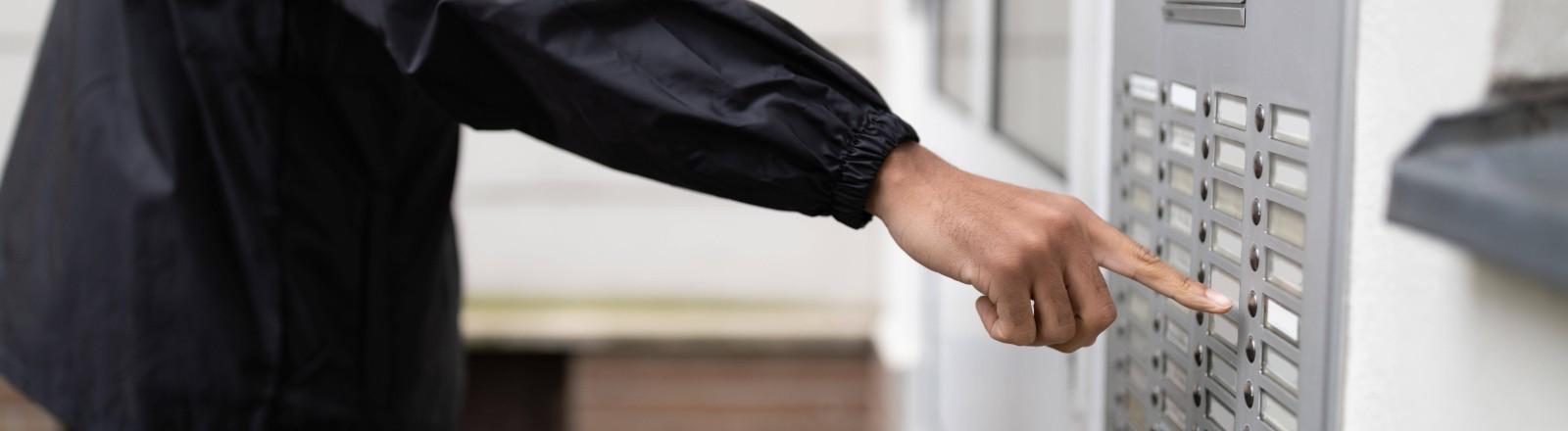 Ein Mann klingelt an einer Mehrfamilienklingel