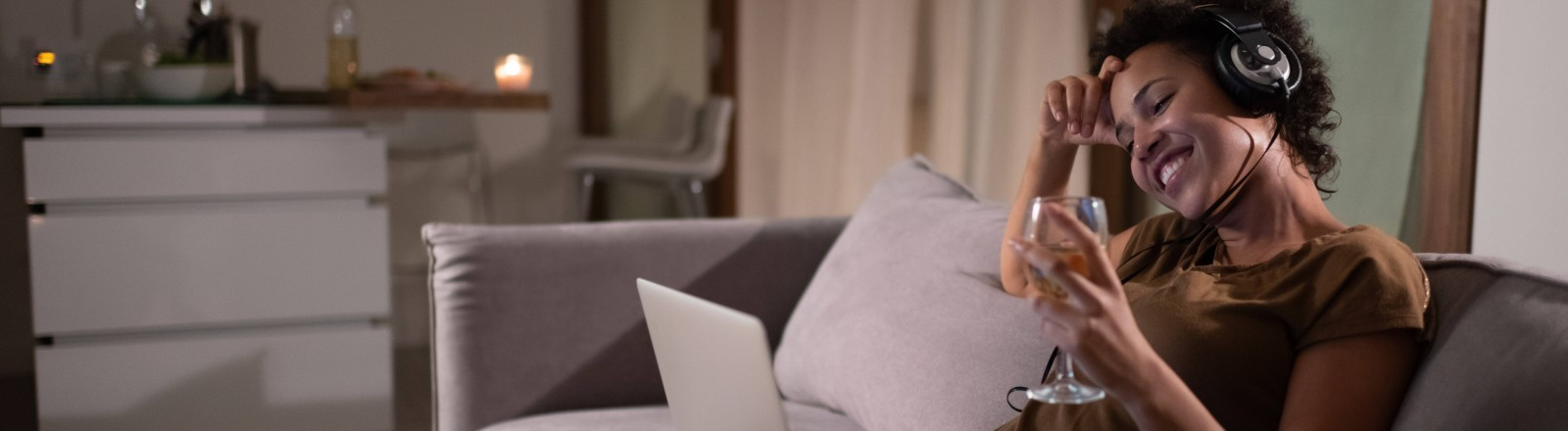 Eine Frau sitzt mit einem Glas Wein und ihrem Laptop auf dem Sofa