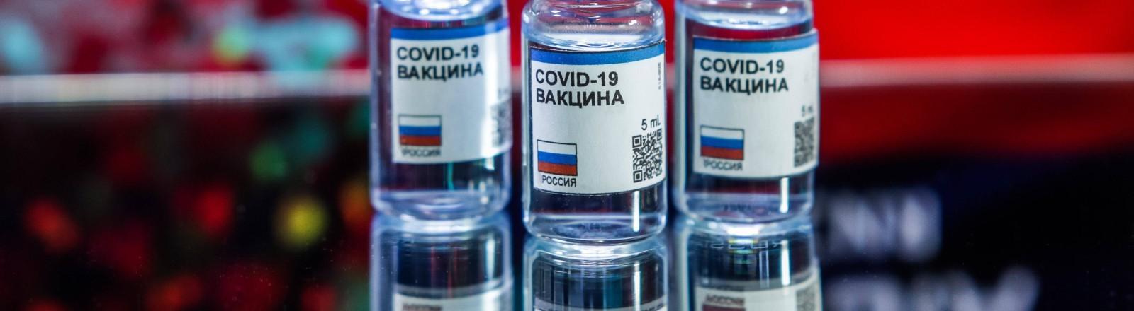 Drei kleine Fläschchen Impfstoff vor einer russischen Flagge