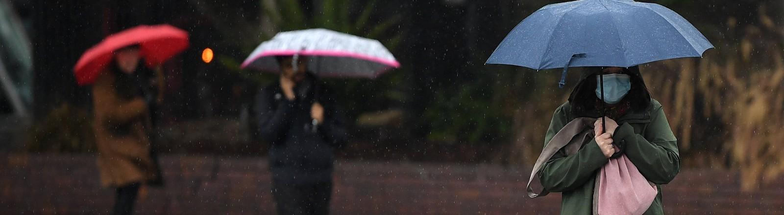 Menschen mit Maske laufen mit Regenschirm im Regen