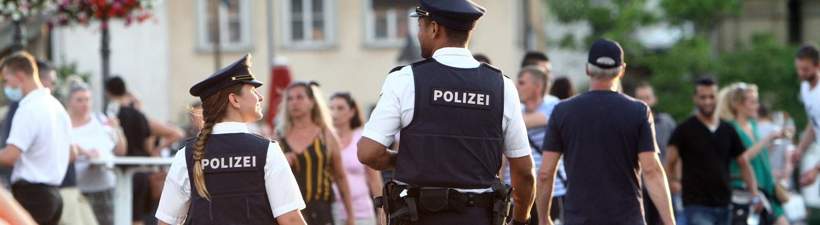 Ein Polizist und eine Polizistin laufen durch eine Fußgängerzone