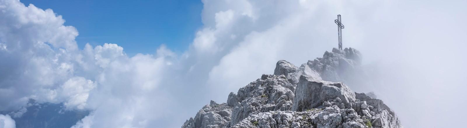 Ein Gipfelkreuz in den Bergen