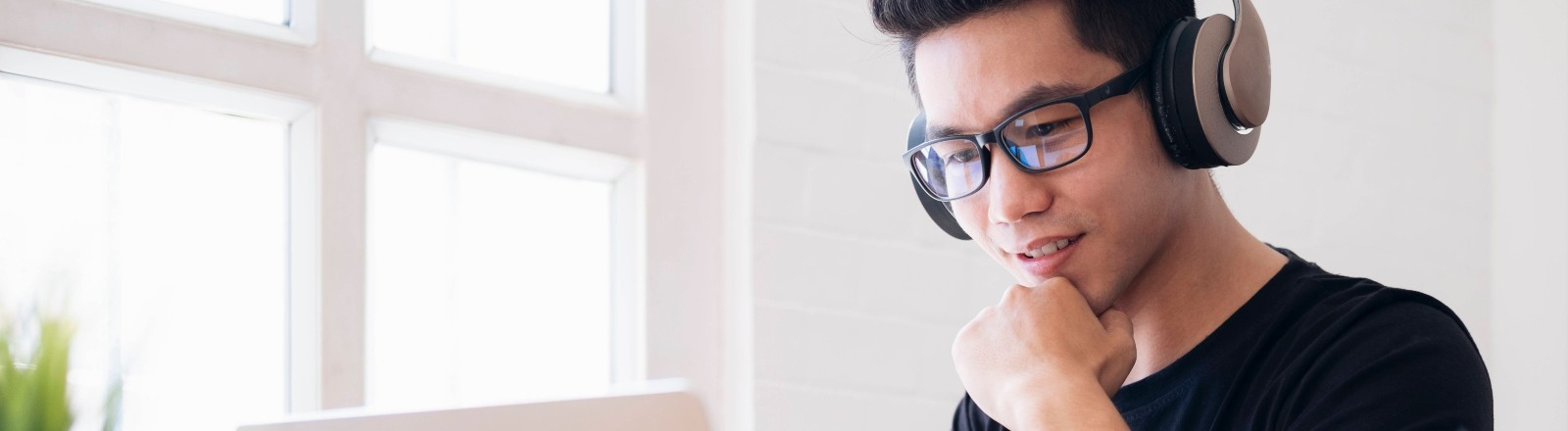 Ein Mann sitzt mit Kopfhörern vor seinem Laptop
