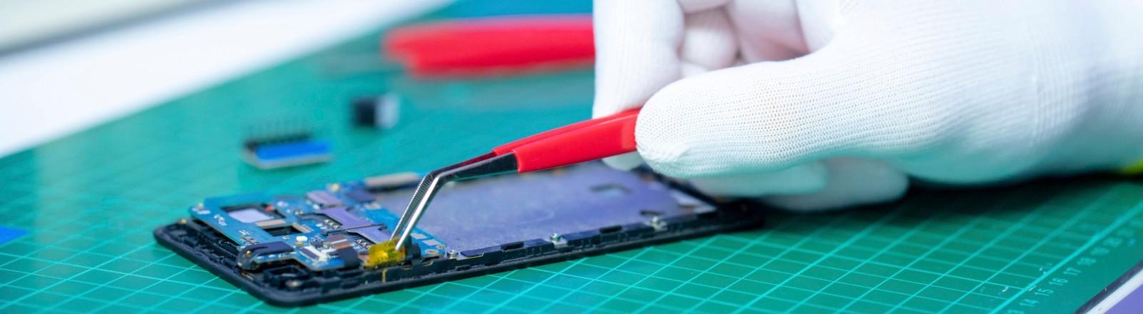 Eine Hand mit weißem Handschuh repariert ein Smartphone