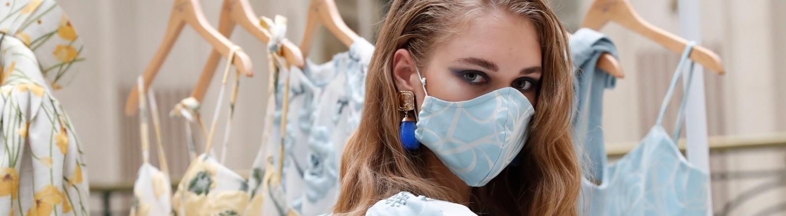 Ein Model trägt eine Maske passend zu ihrem Outfit