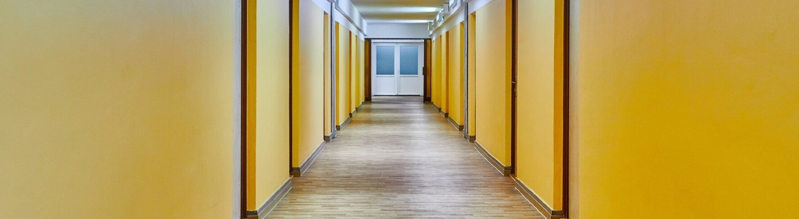 Ein leerer Gang mit gelben Wänden in einem Studierendenwohnheim