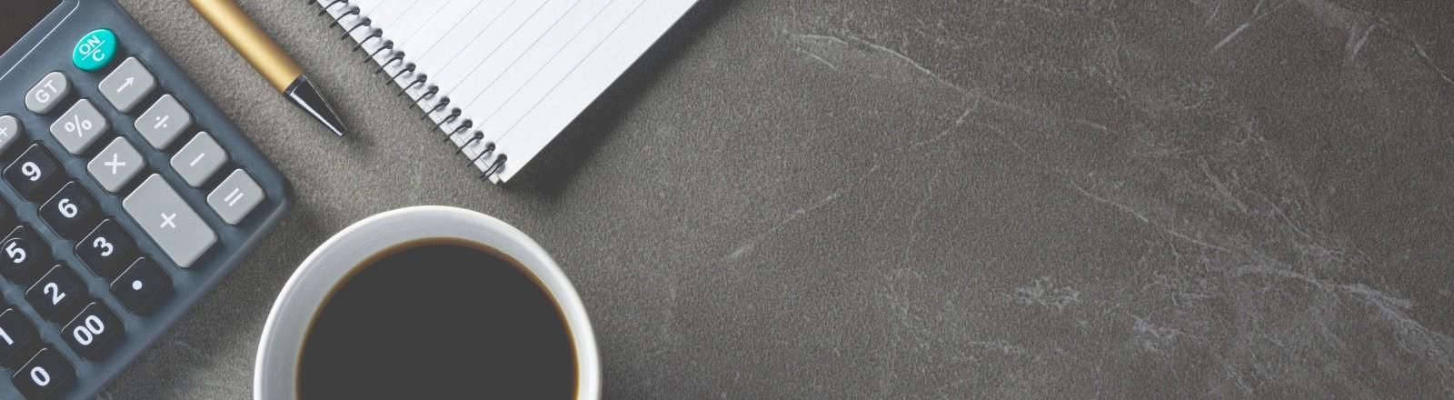 Ein Taschenrechner mit Block und Kaffeetasse