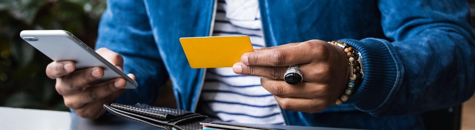 Ein Mann hält sein Smartphone und eine Bankkarte in den Händen