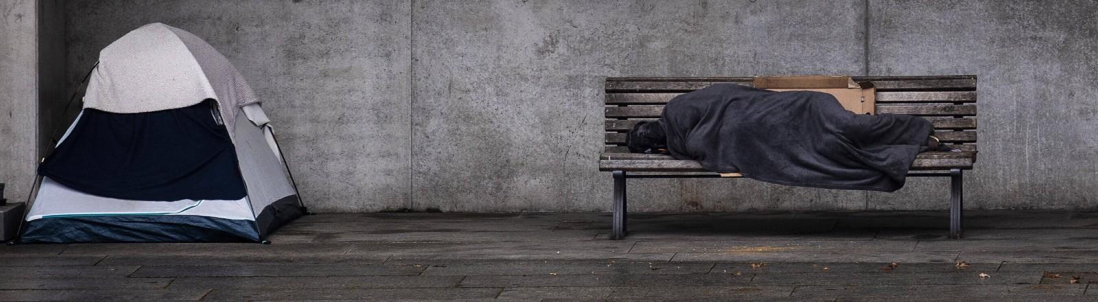 Wohnungslose Person in einer Decke auf einer Bank