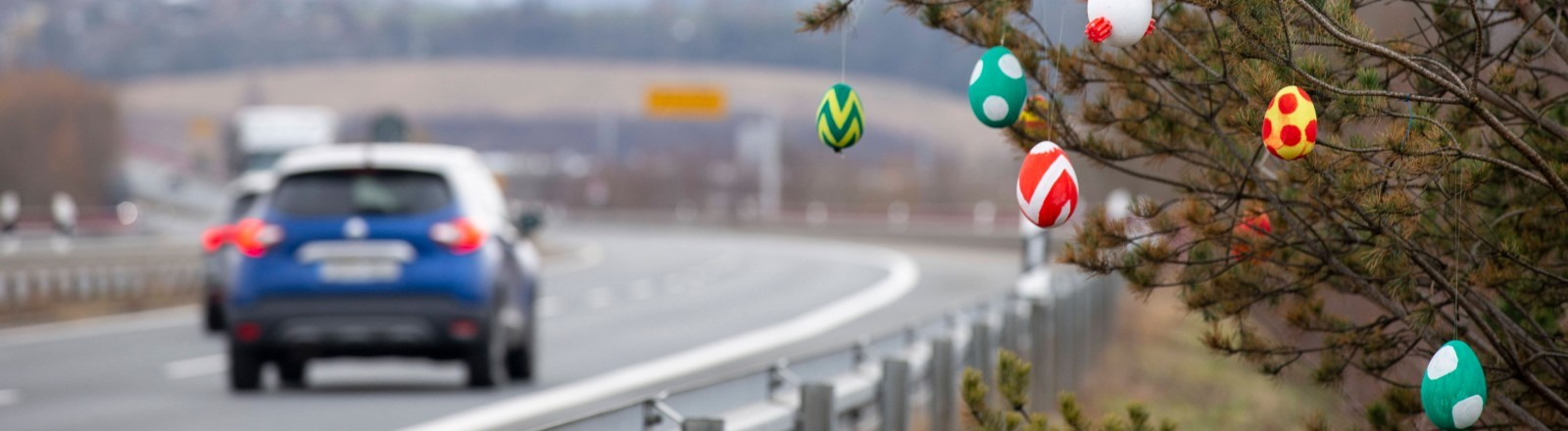 Ein Baum mit Ostereiern an einer Autobahn