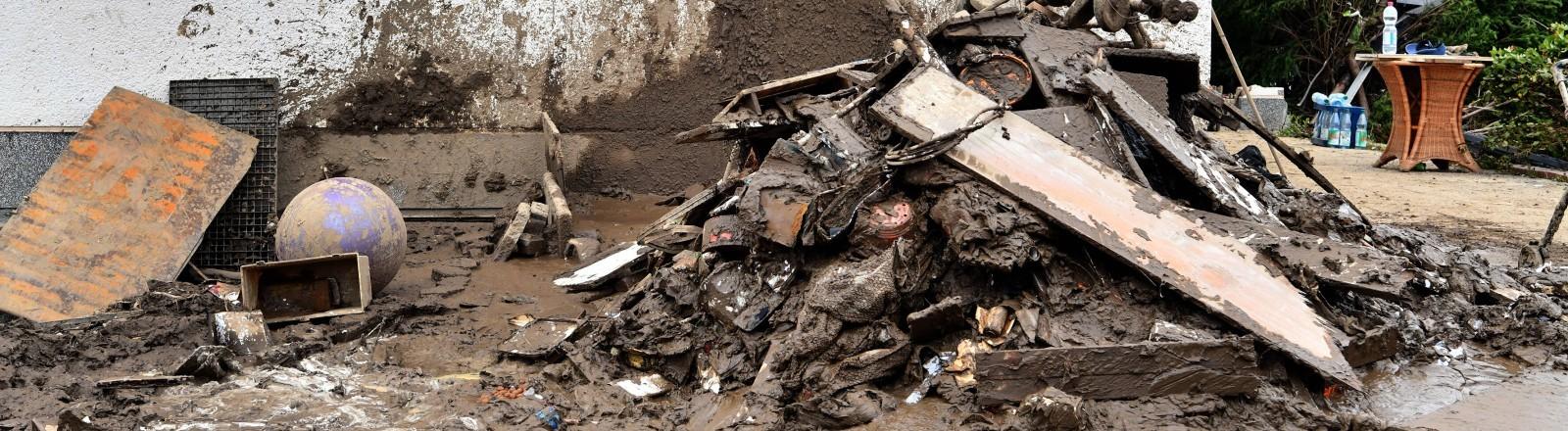 Ein Haus, vor dem sich Schlamm und Müll stapelt