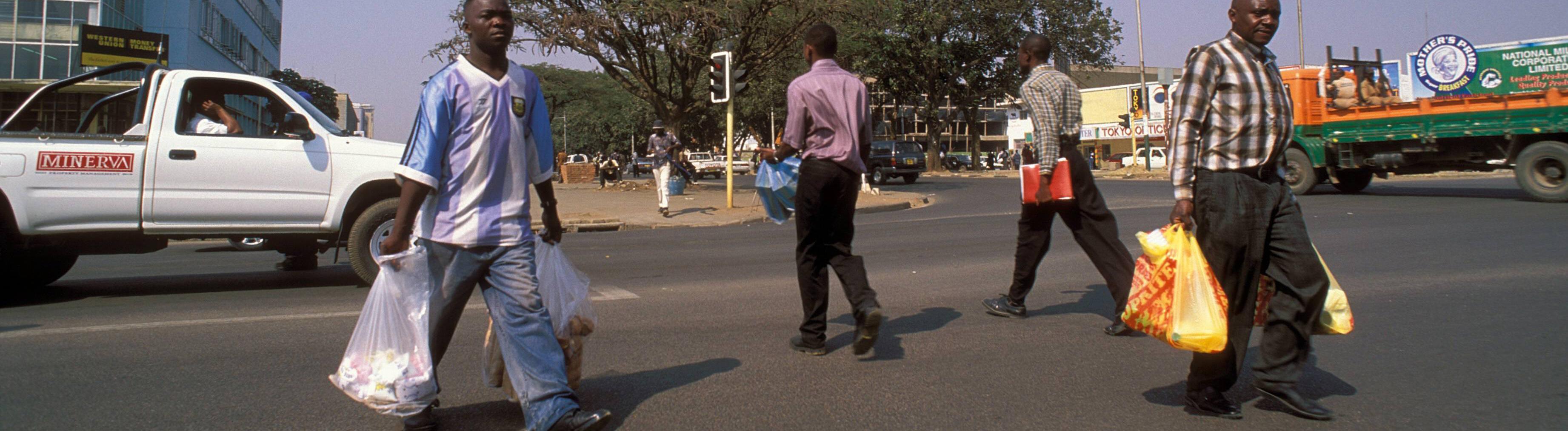 Männer auf einer Straße mit Einkaufstüten im Zentrum von Lusaka in Sambia