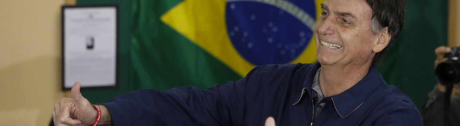 Jair Bolsonaro steht lachend vor einer Brasilienflagge