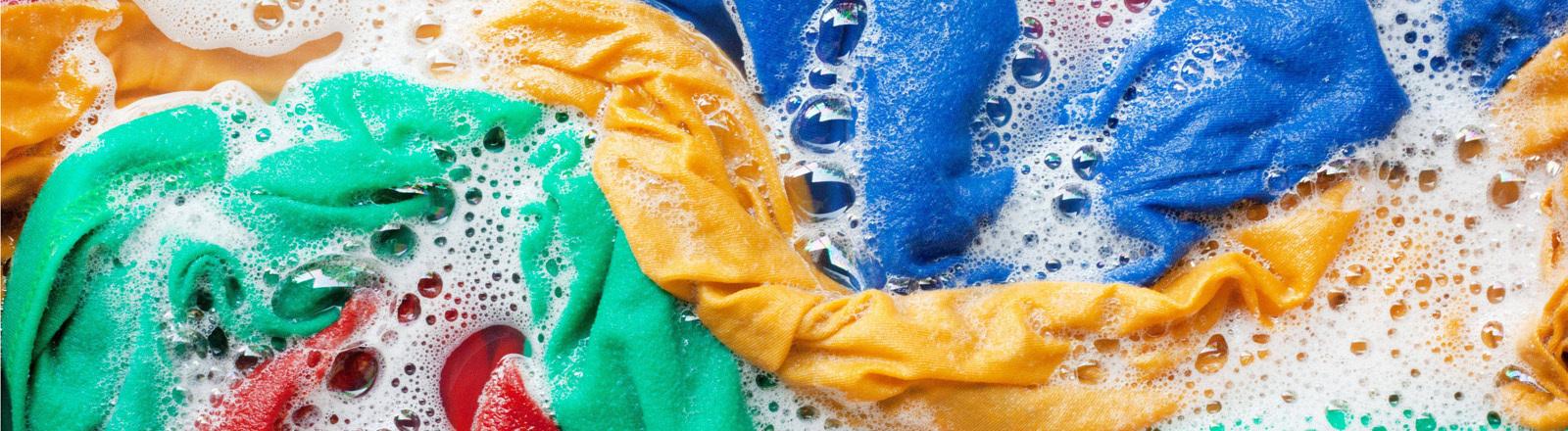 Bunte, nasse Wäsche in Wasser mit Waschmittel.