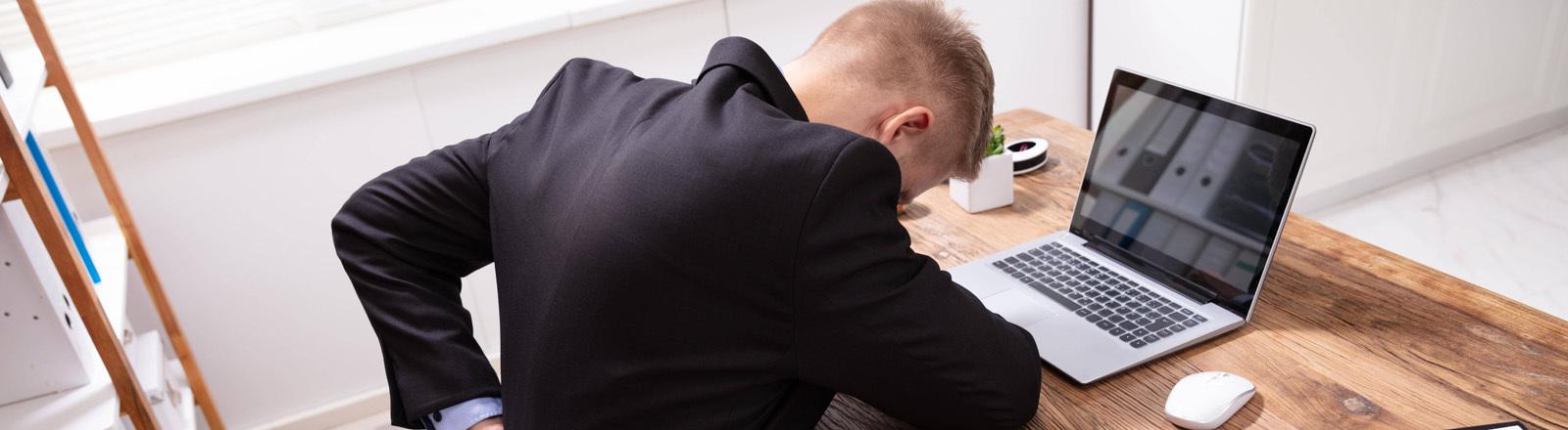 Ein Mann, der am Schreibtisch sitzt, hält sich den unteren Rücken