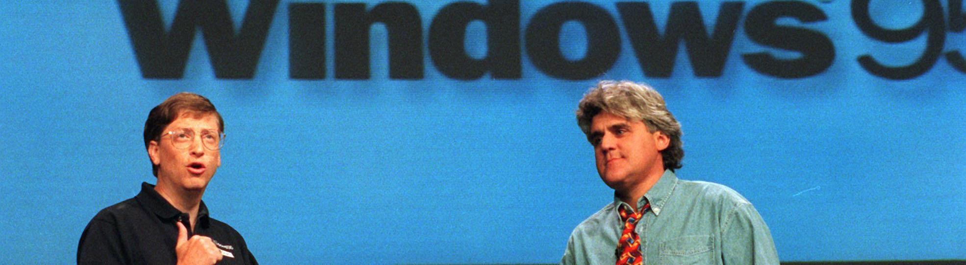 Bill Gates steht mit Jay Leno auf einer Bühne vor dem Windows 95 Logo.