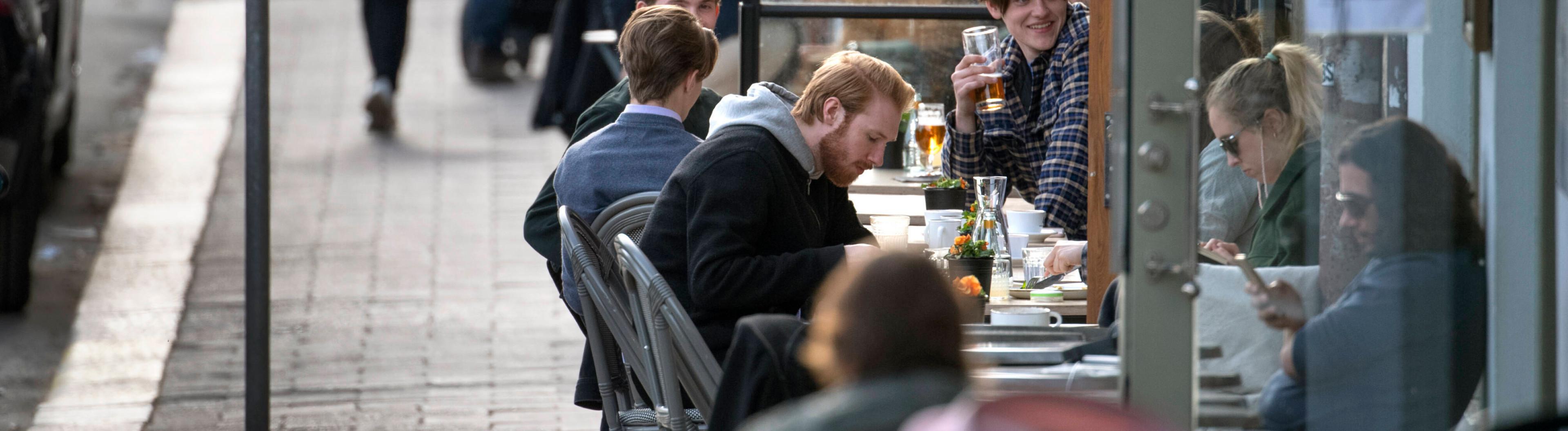Menschen in Stockholm sitzen in Cafe während Corona Pandemie, 20.04.2020