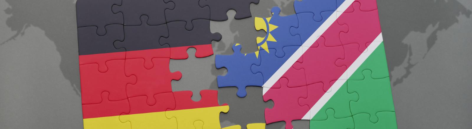 Symbolbild Deutschland und Namibia, Puzzle Nationalflaggen mit Weltkarte