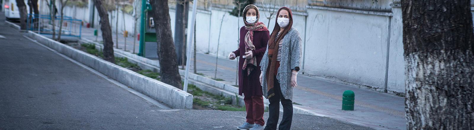 Zwei Frauen mit Mundschutz sind auf den menschenleeren Straßen in der Millionen-Stadt Teheran unterwegs (20.03.2020)