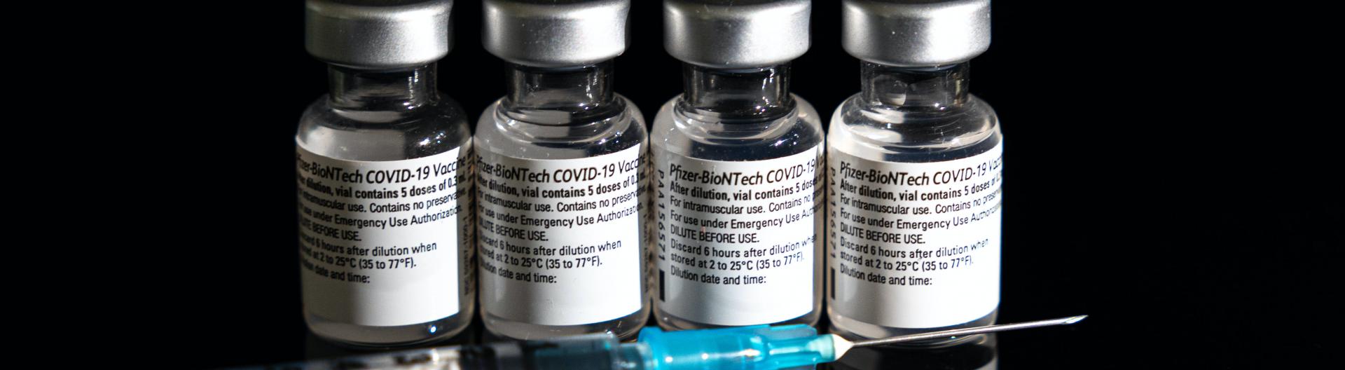Vier Impfdosen von Pfizer-Biontech stehen vor schwarzem Hintergrund mit einer Spritze davor
