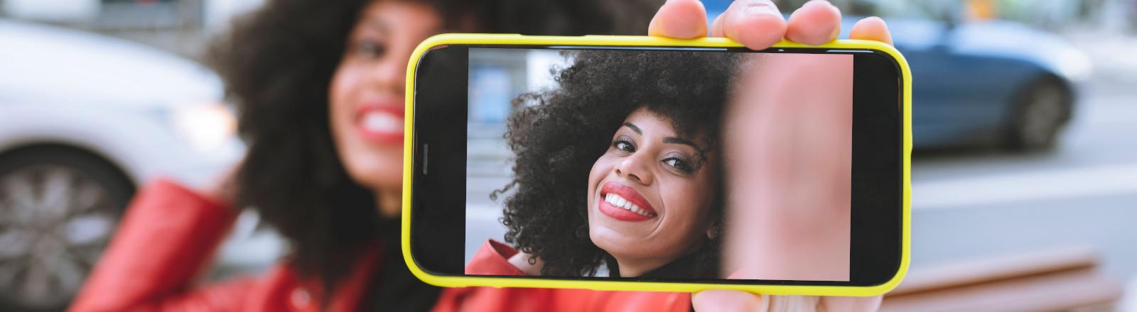 Eine junge Frau macht ein Handyfoto von sich selbst, man sieht sie nur durch den Handybildschirm