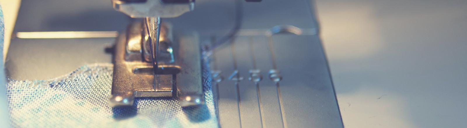 Ein blaugemusterter Stoff liegt unter der Nähnadel einer Nahmaschine.