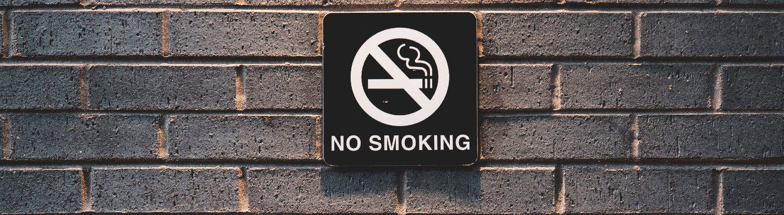 """Ein """"No Smoking"""" Schild auf einer Steinwand"""