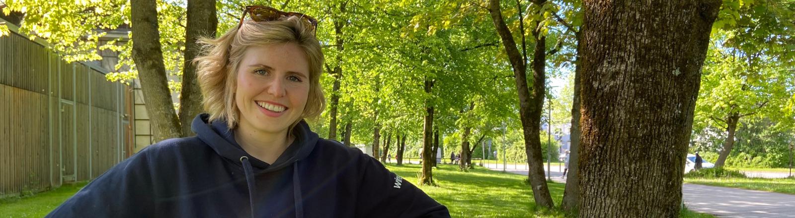 Bild der Gesprächspartnerin Julia, einer jungen Frau mit blonden Haaren. Sie hat einen schwarzen Pulli und eine Sonnenbrille an
