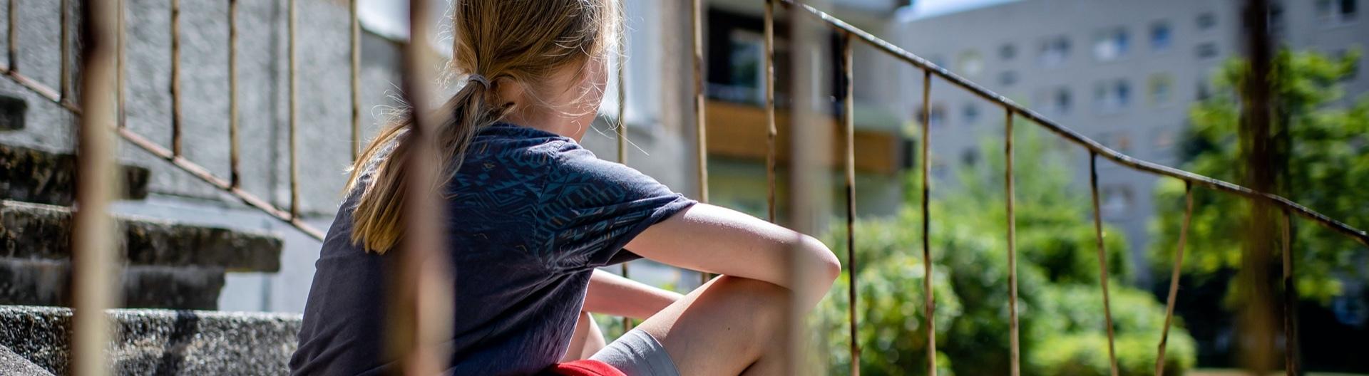 Ein Mädchen sitzt auf Treppenstufen in einer Siedlung in Leipzig