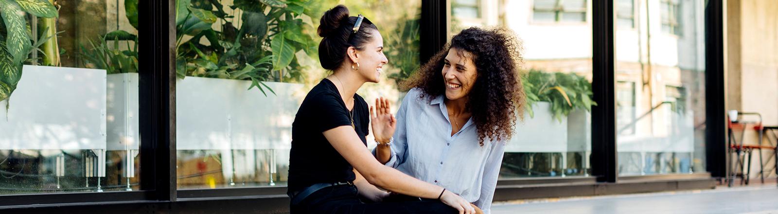 Zwei Frauen sitzen draußen