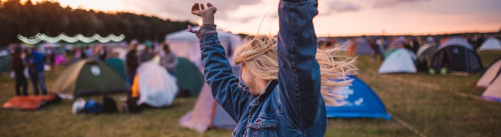 Eine Frau tanzt auf einem Festival Gelände
