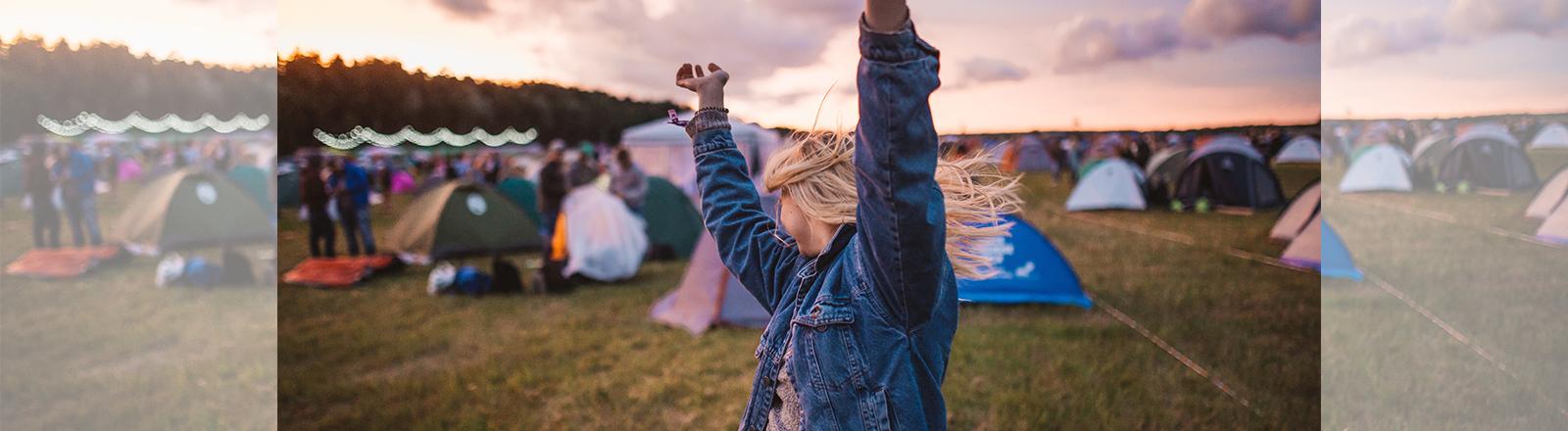 tanzende Frau im Vordergrund, dahinter Zelte