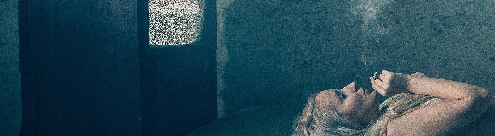 Frau liegt rauchend auf Matraze vor einem alten Fernseher ohne Empfang.