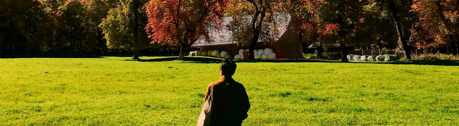 Eine Person steht vor einer Hütte auf dem Land