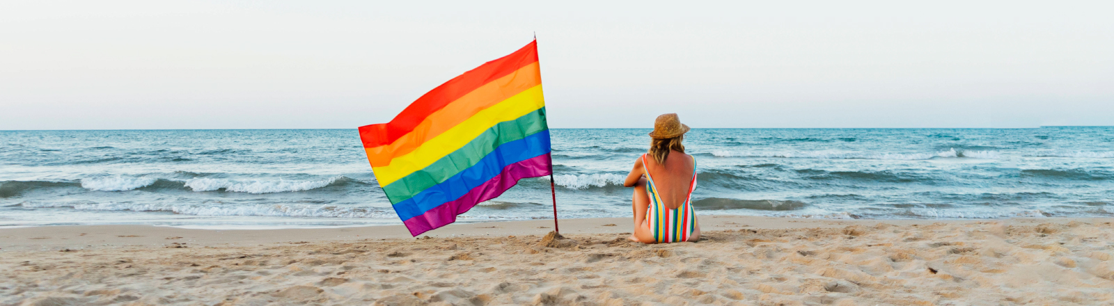 Frau mit Regenbogen-Fahne am Strand