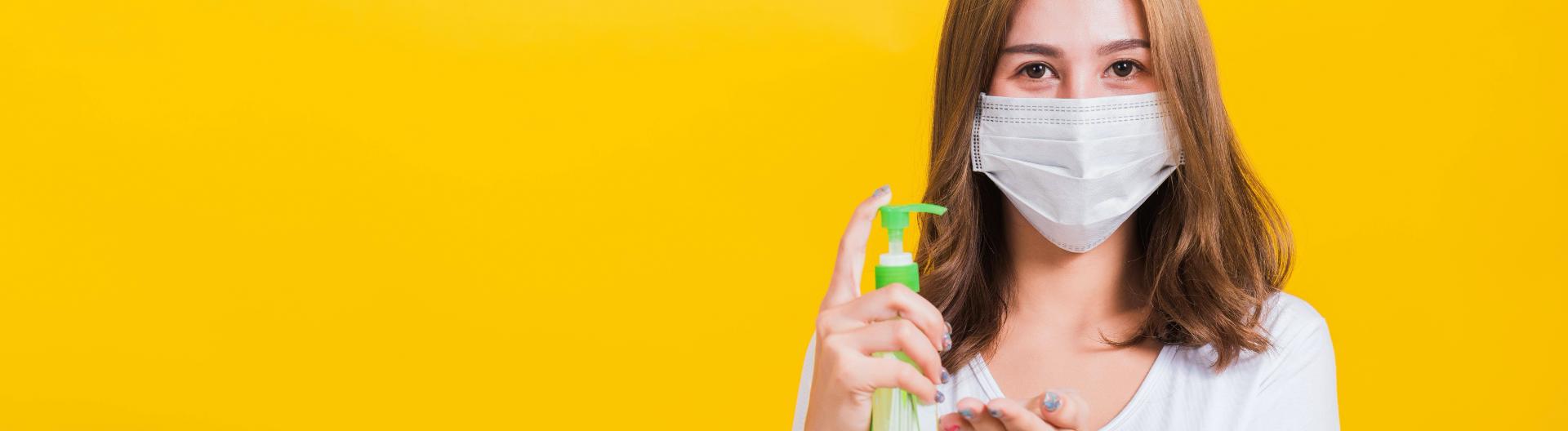Frau mit Mundschutz und Desinfektionsmittel vor gelben Hintergrund