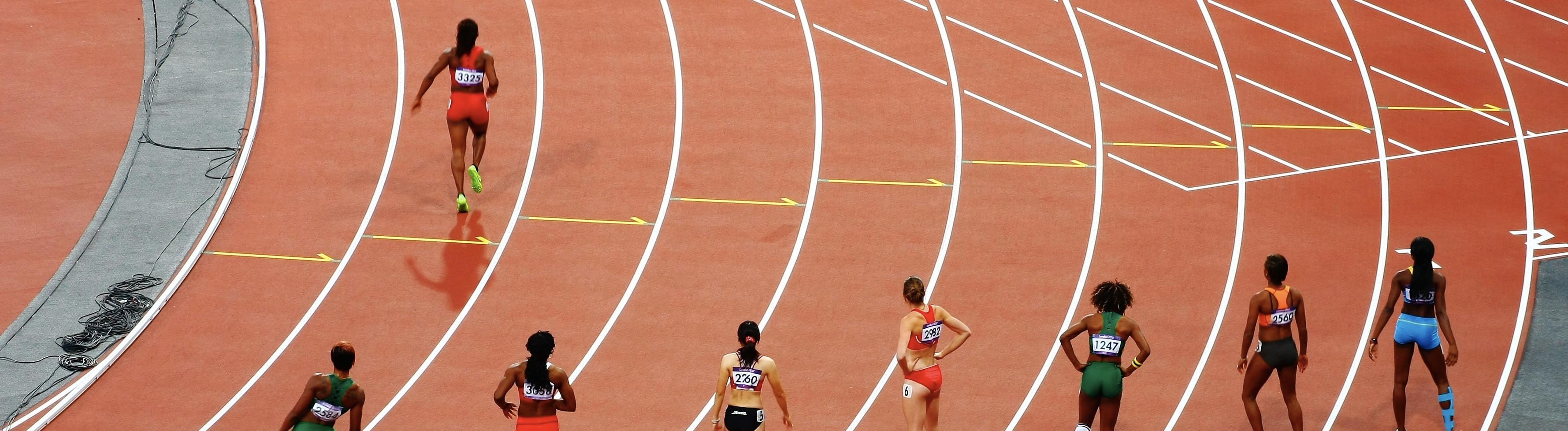Auf einer Rennbahn stehen Athletinnen auf ihren Startpositionen