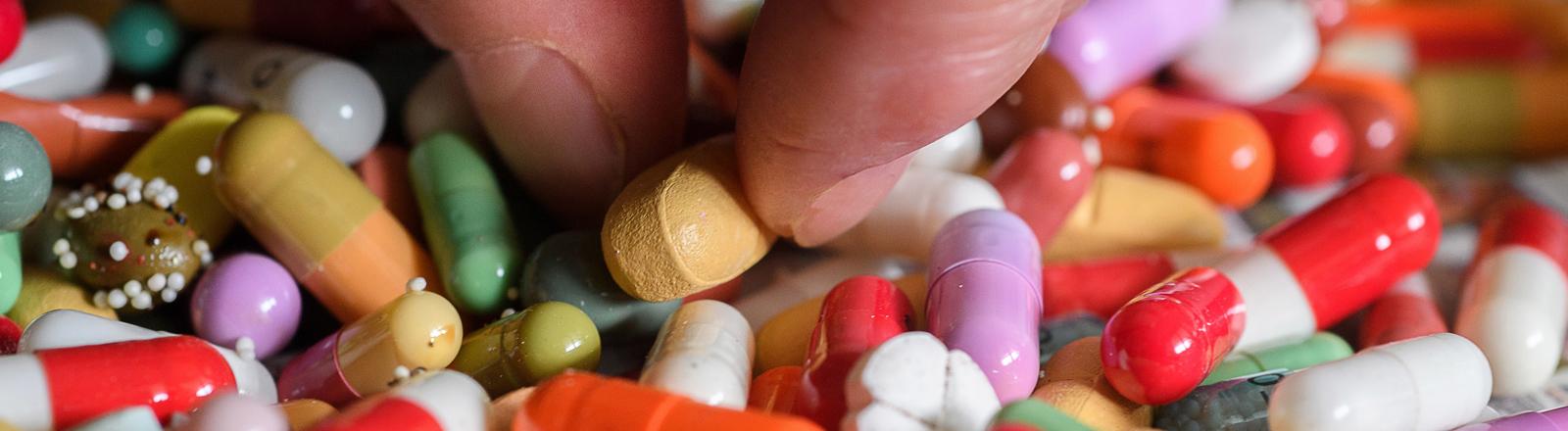 Eine Hand nimmt Tabletten zwischen die Finger