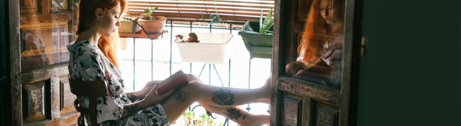 Frau sitzt alleine am Balkon und liest