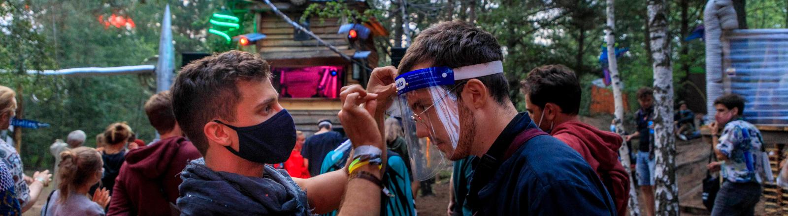 Szene beim Festival Milde Möhre während der Corona-Pandemie: Ein Mann zieht einem anderen Mann einen Plastikschutz an