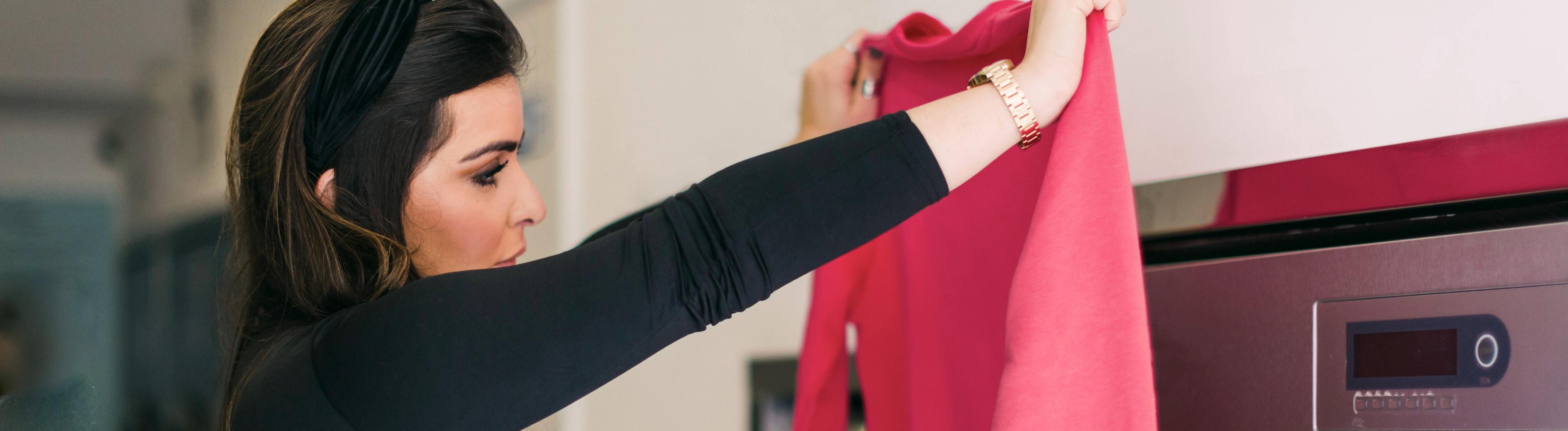 Frau steht vor Waschmaschine und hält pinken Pulli hoch