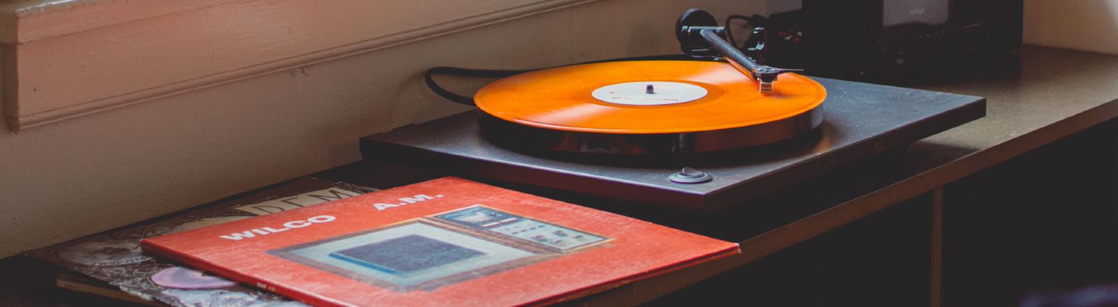 Ein Plattenspieler mit orangener Schallplatte in einem Wohnzimmer