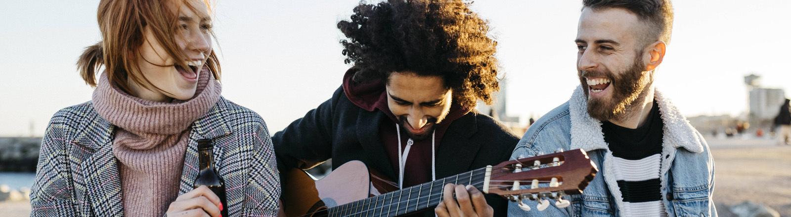 Drei junge Leute lachen mit Gitarre