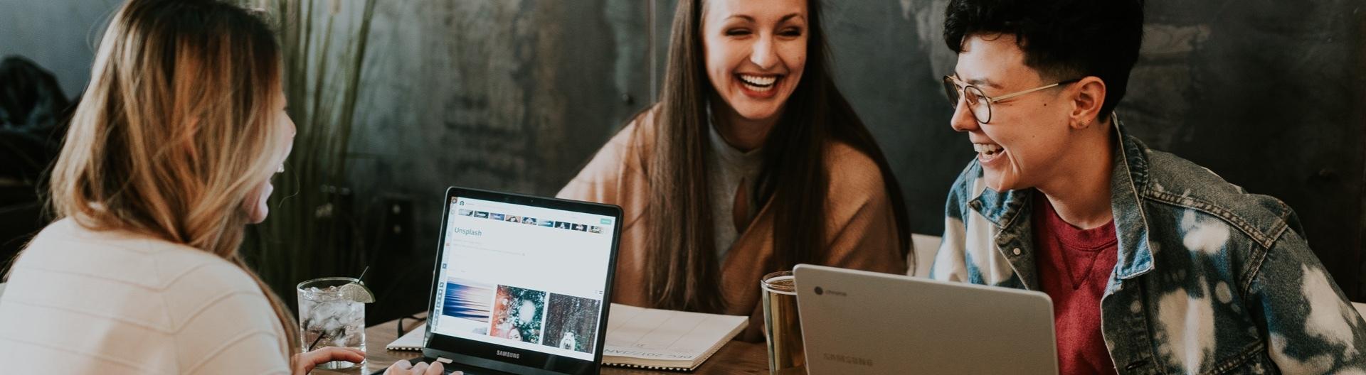 Drei Frauen sitzen an einem Tisch mit zwei Laptops und lachen sich an