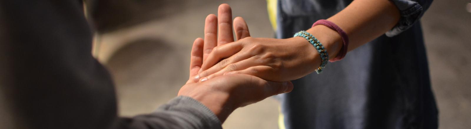Eine Frau schlägt in eine andere Hand ein