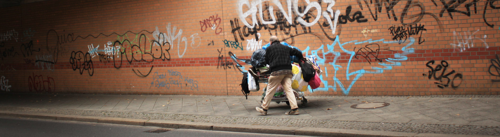 Ein wohnungsloser Mann mit einem Einkaufswagen auf der Straße