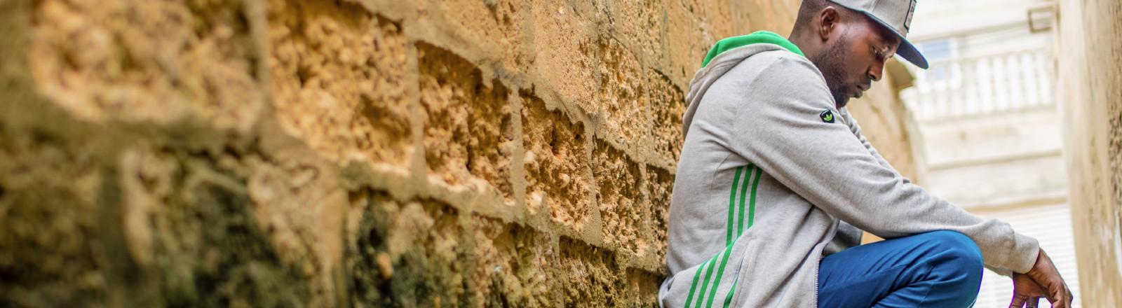 Mann hockt an Mauer gelehnt und denkt nach.
