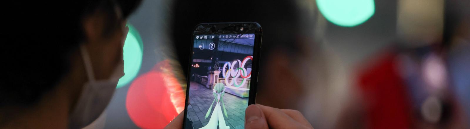 Ein Mann hält sein Smartphone um die Olympia Installation zu sehen, 21.07.2021 Tokio