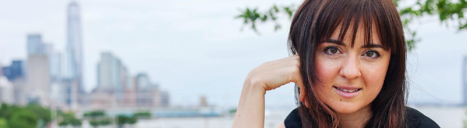 Die Gesprächspartnerin Paulina, eine brünette Frau Anfang 30, posiert vor der New Yorker Skyline