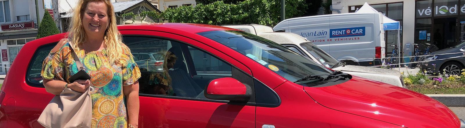 Nathalie vor einem Auto, das sie bei OuiCar vermietet.